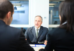 Businessman talking to a couple in a office