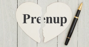 Heart-shape card on weathered wood background with text Prenup