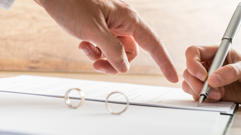 Male hand pointing to a divorce paper